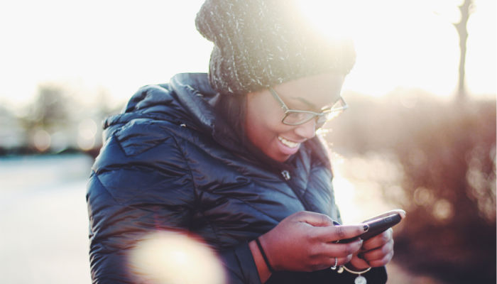 woman smiling at her phone texting and ministering during a pandemic