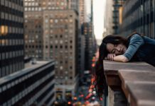 woman asleep on the side of tall building