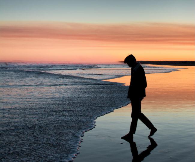a man walking along the beach at sunset
