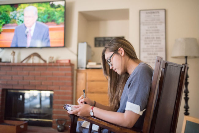 young woman listens to general conference for the church