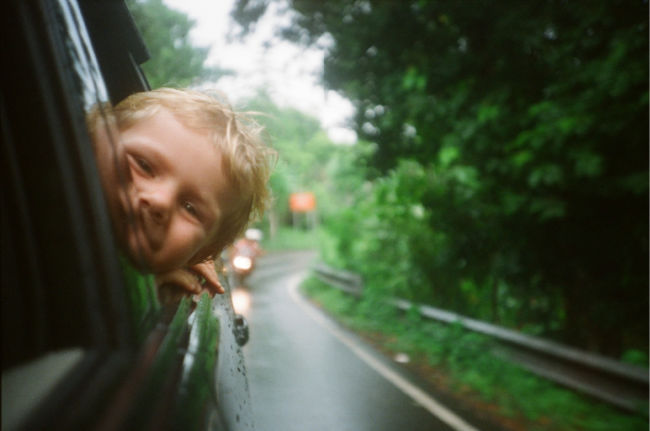 child with his head out the window while driving