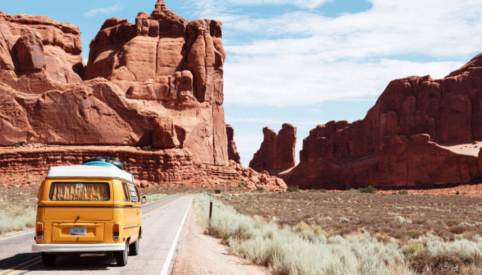volkswagen bus driving towards red rock on a road trip