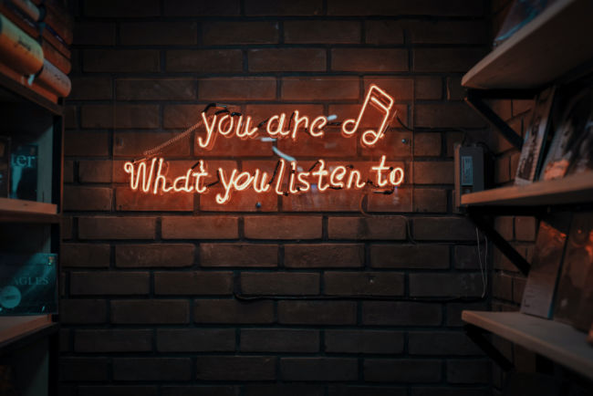 neon sign that says you are what you listen to regarding podcasts