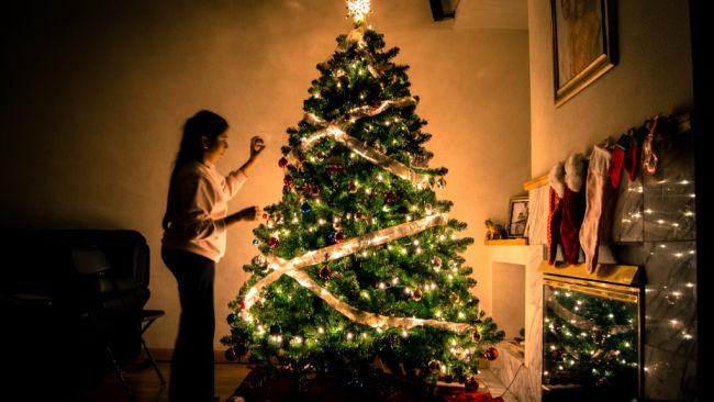 young woman putting lights on christmas tree