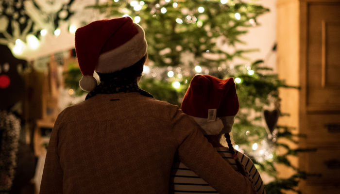 mother and daughter sit together next to a christmas tree while wearing santa hats