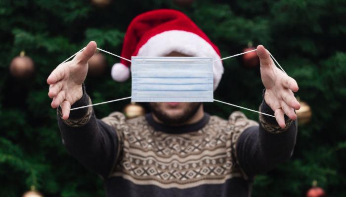 man holding up mask covid-19 christmas wearing a santa hat