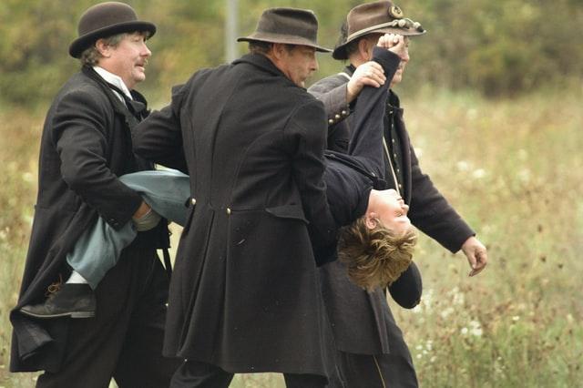 period photo men carrying boy to punishment
