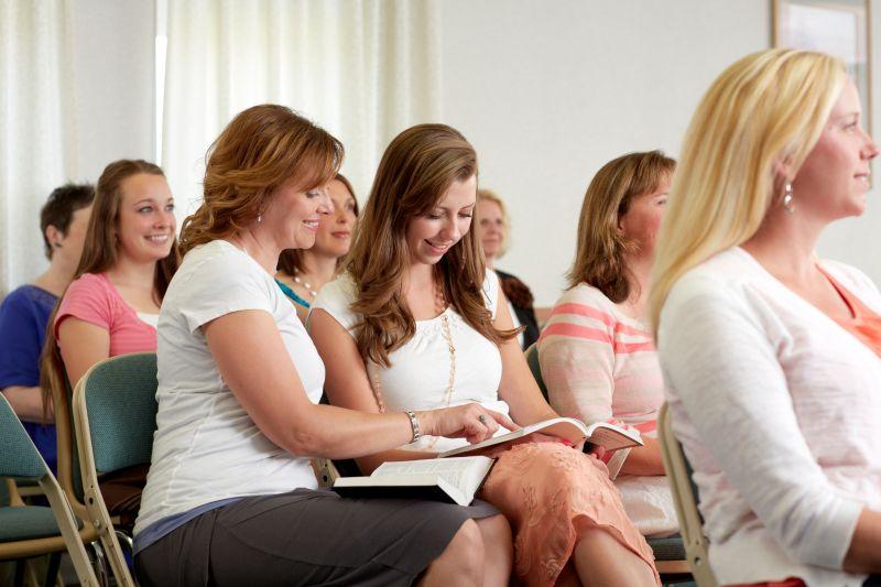 Dos mujeres se sientan juntas durante la Sociedad de Socorro.  Asistir a las reuniones de la iglesia es una parte importante para fortalecer nuestro testimonio.
